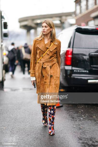 Camille Charriere wears a brown/orange suede trench coat floral print colored boots outside Coach during New York Fashion Week Fall Winter 2020 on...