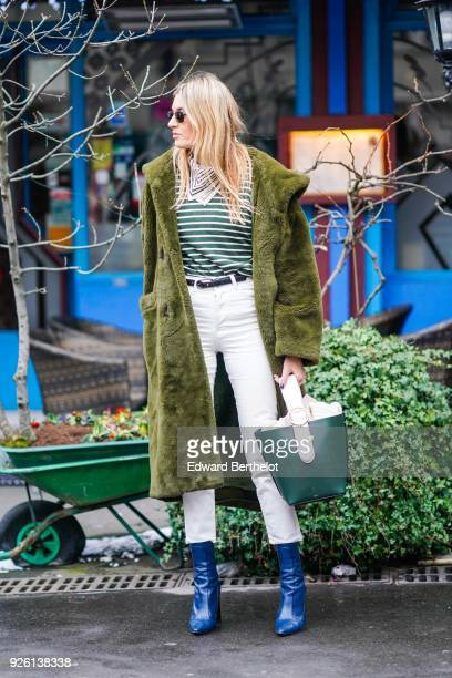Camille Charriere wears a green fluffy coat a bandanna a striped top white pants blue shoes a green bag during Paris Fashion Week Womenswear...