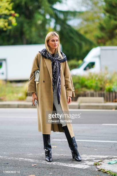 Camille Charriere wears a long scarf, a beige long wool coat, a bag, white pants, black leather high boots, outside Hermes, during Paris Fashion Week...