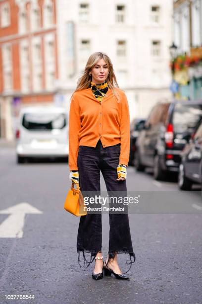 Camille Charriere wears an orange jacket black ripped pants an orange bag during London Fashion Week September 2018 on September 15 2018 in London...