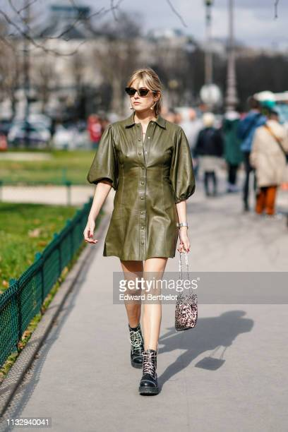 Camille Charriere wears earrings a green leather dress a bag black leather shoes sunglasses outside Paco Rabanne during Paris Fashion Week Womenswear...