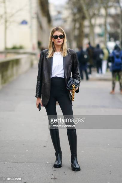 Camille Charriere wears Ray-Ban sunglasses, a black leather jacket, a white t-shirt, a Bottega Veneta leather bag with a golden chain handle, black...