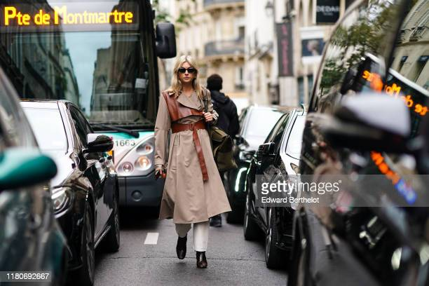 Camille Charriere wears sunglasses a beige trench coat with brown leather parts a large belt black shoes a khaki bag outside Thom Browne during Paris...