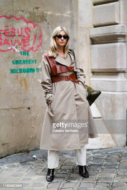 Camille Charriere wears sunglasses, a beige trench coat with brown leather parts, a large belt, black shoes, a khaki bag, outside Thom Browne, during...