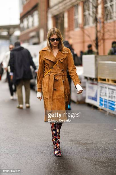Camille Charriere wears sunglasses a brown/orange suede trench coat floral print colored boots outside Coach during New York Fashion Week Fall Winter...