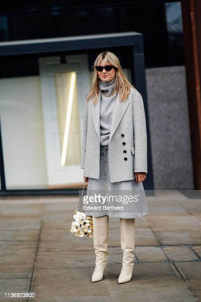 Camille Charriere wears sunglasses, a light grey turtleneck, a light grey jacket, a light grey skirt, a shiny golden sequined bag, beige pointy...