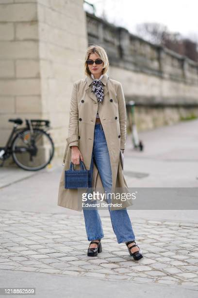 Camille Charriere wears sunglasses, a trench coat, blue denim jeans pants, a Dior blue mini shopping bag, black shoes, a scarf, outside Dior, during...