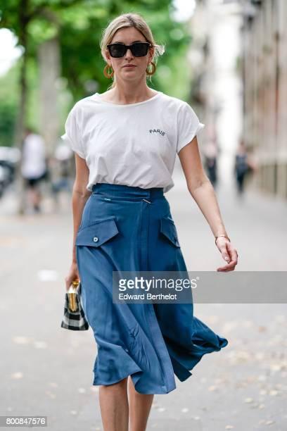 Camille Charriere wears sunglasses a white tshirt a blue skirt a vichy gingham bag black shoes outside the Paul Smith show during Paris Fashion Week...