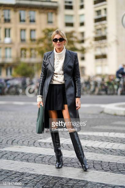 Camille Charriere wears sunglasses, a white wool pullover, a black leather long coat, a black short pleated skirt, leather boots, outside Coperni,...