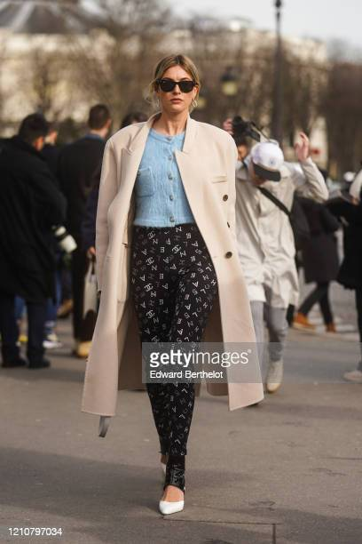 Camille Charriere wears sunglasses, earrings, a beige long coat, a blue fluffy jacket, Chanel pants with printed monograms logos, white pointy shoes,...