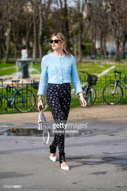 Camille Charriere wears sunglasses, earrings, a blue fluffy jacket, Chanel logo printed pants, pointy shoes, a bag, outside Chanel, during Paris...