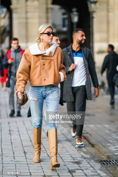 Camille Charriere wears sunglasses earrings a brown aviator jacket with sheep white wool inner lining ripped blue denim jeans a Vuitton bag beige...