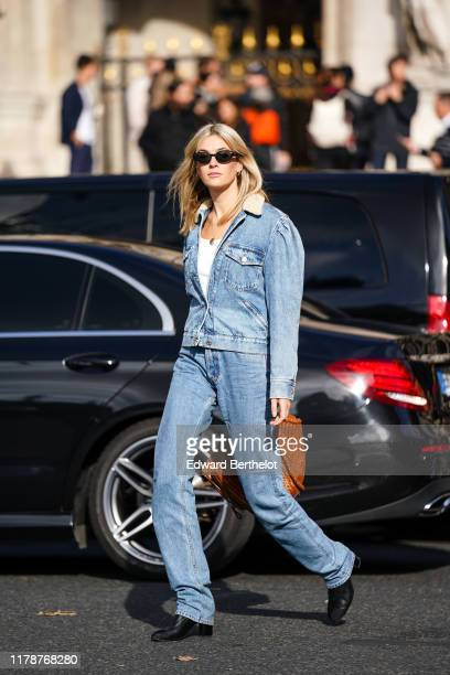 Camille Charrière wears earrings, sunglasses, a white top, a washed-out light blue denim jacket with a cream-color fluffy collar, washed out light...
