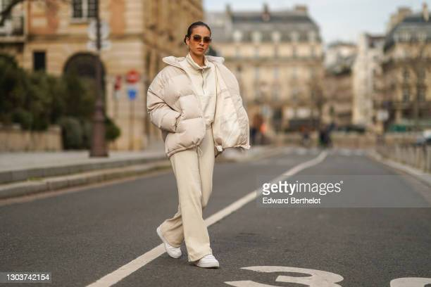 Camille Coyere wears sunglasses, a white oversized winter puffer long coat, a white pullover with a front zipper, white flared pants, white Nike...
