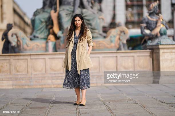 Camille Grandguillote aka Camille GrandXo wears a blue long flowing floral print v-neck dress from Sezane, a beige trench coat from Asos, beige and...