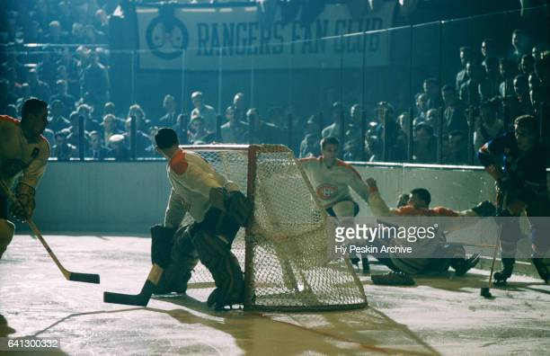 Camille Henry of the New York Rangers skates with the puck around the net as goalie Jacques Plante of the Montreal Canadiens tries to follow the puck...