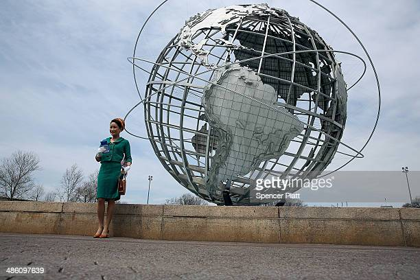 Camille Hsiung dressed in 1960's clothes poses in front of the Unisphere with a vintage Life magazine during festivities marking the 50th anniversary...