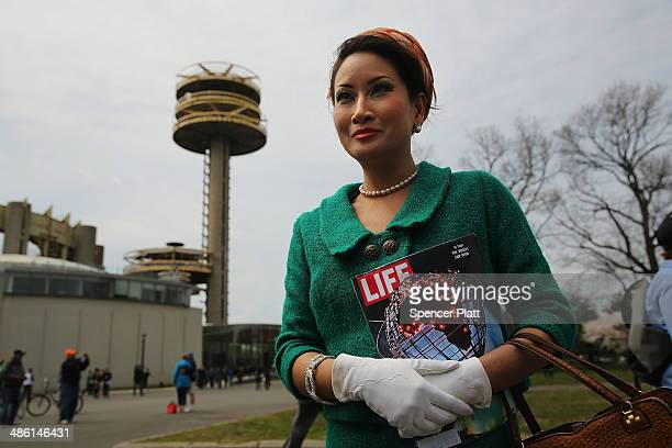 Camille Hsiung dressed in vintage 1960s clothes poses in front of the Unisphere with a Life magazine of the period during festivities marking the...