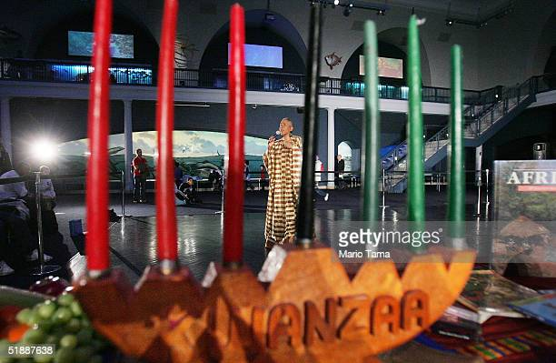 Camille Yarborough sings African music behind a traditional 'kinara' candelabra during a news preview of the 'Kwanzaa 2004 We Are Family' festival at...