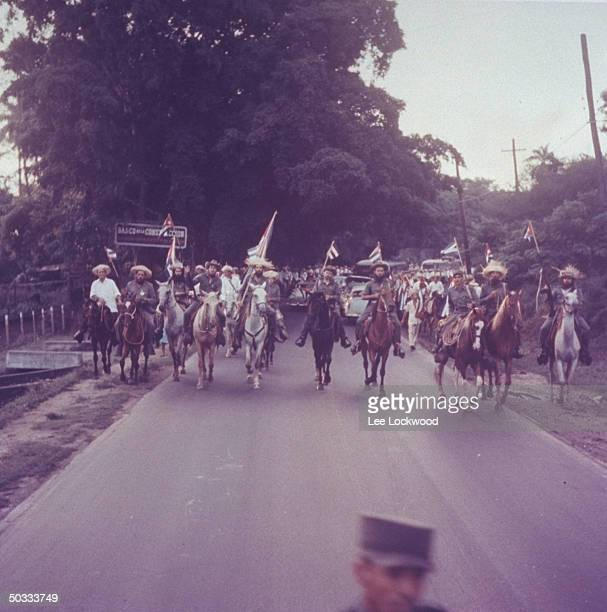 Camilo Cienfuegos proCastro rebel army leader wsome of his troops riding on horseback triumphantly into city on day of huge victory celebration