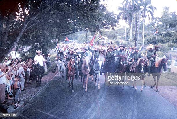 Camilo Cienfuegos proCastro rebel army leaderwaving wsome of his troops riding horseback triumphantly into city on day of huge victory celebration