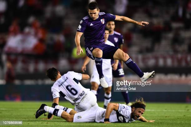 Camilo Mayada of River Plate fights for the ball with Jose Bonifacio and Facundo Oreja of Gimnasia during a match between River Plate and Gimnasia y...