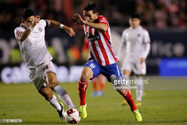 Camilo Mayada of San Luis struggles for the ball with Jesus Antonio Molina of Chivas the 4th round match between Atletico San Luis and Chivas as part...