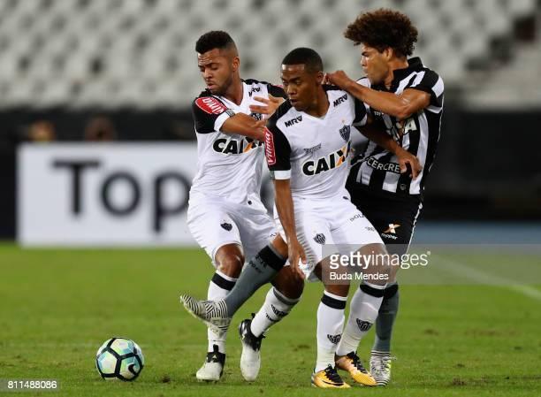 Camilo of Botafogo struggles for the ball with Rafael Carioca and Elias of Atletico MG during a match between Botafogo and Atletico MG as part of...
