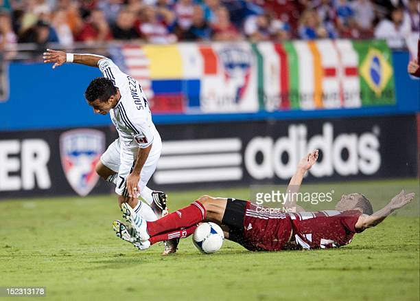 Camilo Sanvezzo of the Vancouver Whitecaps FC is tackled by Matt Hedges of FC Dallas on September 15 2012 at FC Dallas Stadium in Frisco Texas