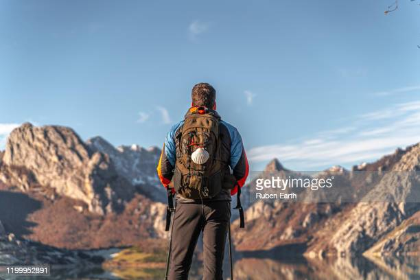 camino de santiago hiker with backpack and shell looking at the landscape - camino de santiago stock pictures, royalty-free photos & images