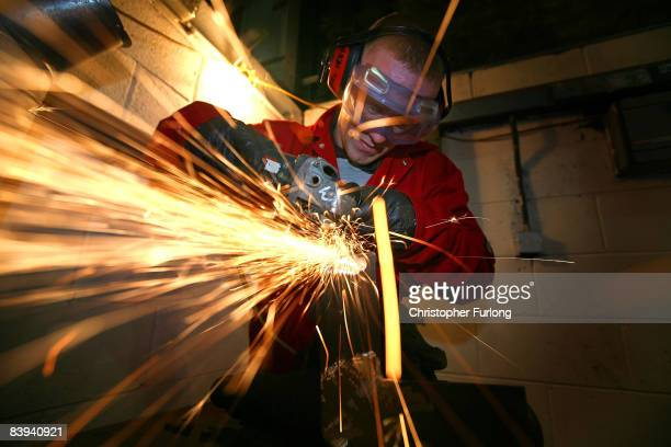 Cammell Laird apprentice Bryn Jones aged 19 works on a grinding machine at the company's shipyard where he is learning traditional ship building...