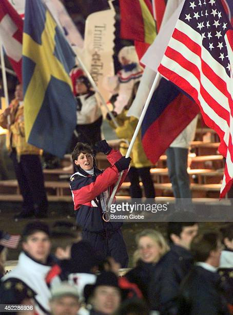 Cammi Granato of the US women's gold medal hockey team carries the US flag into Olympic stadium at the start of closing ceremonies