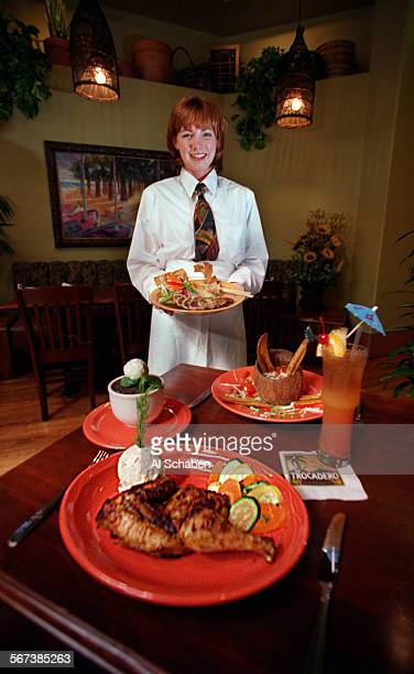 CAmojo20705AS––IRVINE––Clockwise from bottom roast chicken chocolate souffle cake server Teri DeSimone holds a dish of Ahi South American style bay...