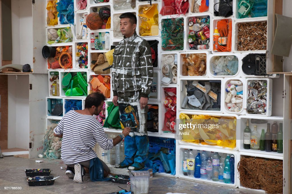 Camouflage artist Liu Bolin at the Surfrider Foundation in Biarritz, blended into a background of rubbish collected on the Basque Coast with the aim of denouncing marine pollution ().