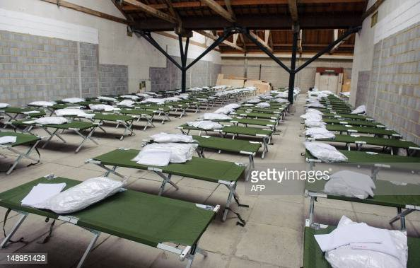 Camp Beds Are Lined Up In The Sleeping Quarters At A