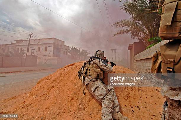 camp corregidor, ramadi, iraq, may 20, 2006 - links from his ammo belt and brass fly as a soldier lays down a vicious barrage of gun fire on insurgent positions to cover u.s. marines movements while on patrol in the city of ramadi. - corregidor_(position) stock pictures, royalty-free photos & images