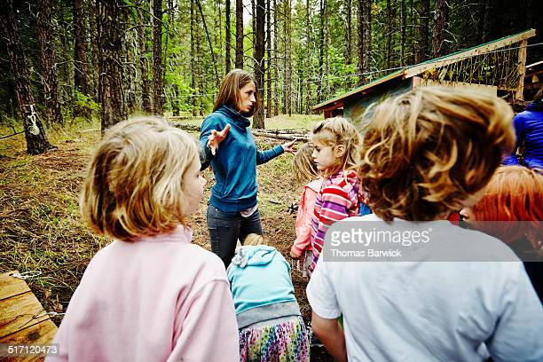 Camp counselor giving instructions to kids