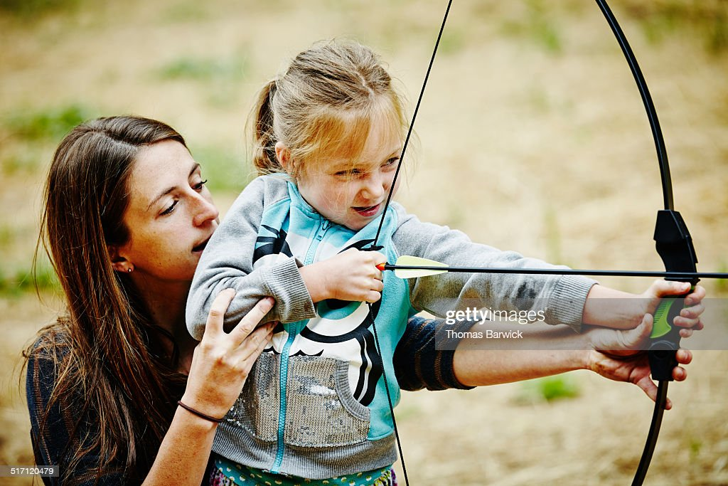Camp counselor helping girl shoot bow and arrow : Stock Photo