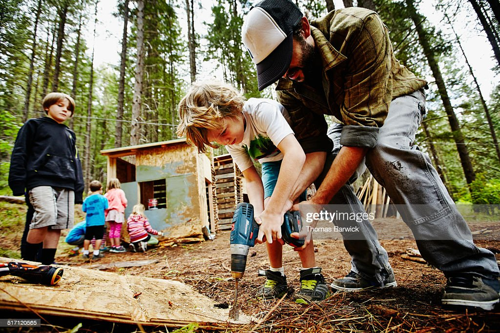 Camp counselor helping young boy use drill : Stock Photo