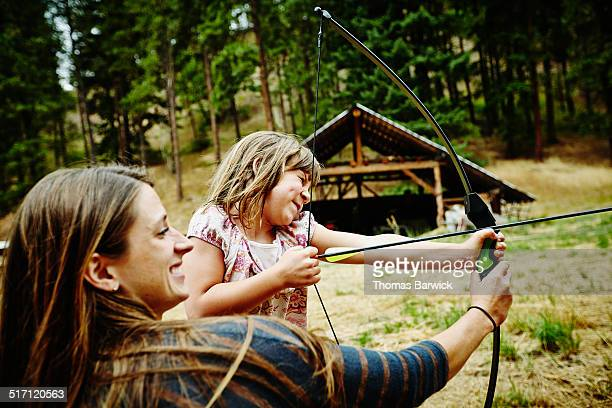 Camp counselor helping young with bow and arrow