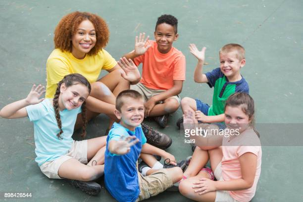 Camp counselor, multi-ethnic children sitting in circle