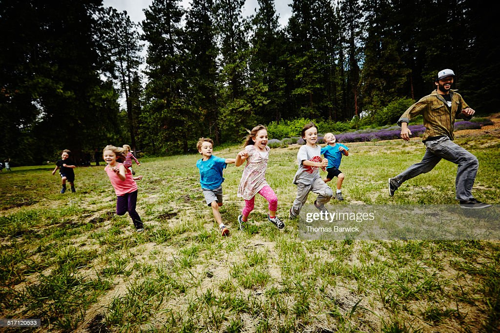 Camp counselor playing tag with young kids : Stock Photo