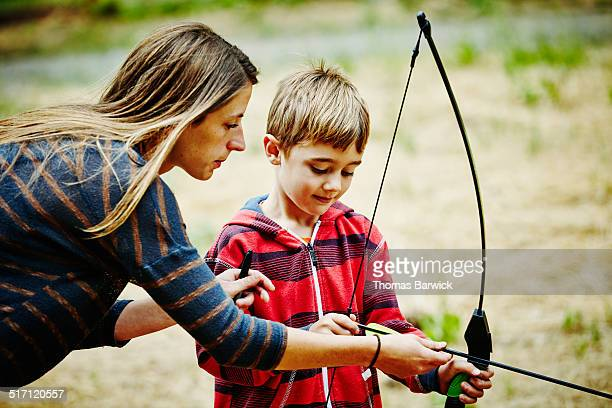 Camp counselor teaching boy to shoot bow and arrow