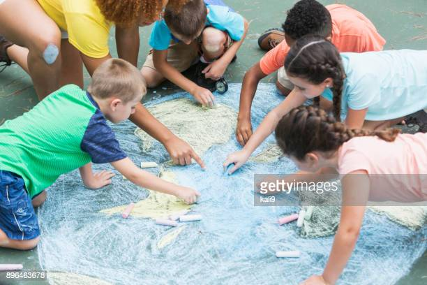 camp counselor with children, chalk drawing of earth - giornata mondiale della terra foto e immagini stock