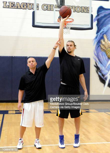 Camp Director Geoff Golden left uses NBA player Louis Amundson to demonstrate the proper form for shooting a basketball on Monday June 18 during a...