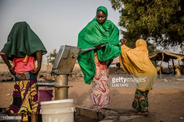 TOPSHOT Camp dwellers pump water from a well at Malkohi refugee camp in Jimeta Adamawa State Nigeria on February 19 four days ahead of the country's...