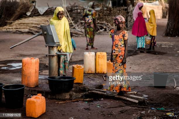 Camp dwellers pump water from a well at Malkohi refugee camp in Jimeta Adamawa State Nigeria on February 19 four days ahead of the country's General...