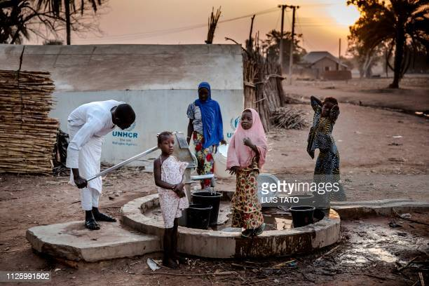 Camp dwellers pump water from a well in the early morning at Malkohi refugee camp in Jimeta Adamawa State Nigeria on February 19 four days ahead of...