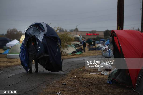 Camp Fire evacuee carries his tent as rain falls at a temporary evacuation center next to a Walmart store on November 21 2018 in Chico California...
