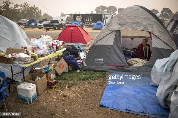 A Camp Fire evacuee sits in a tent in a makeshift tent city in Chico California US on Thursday Nov 15 2018 The number of acres burned in the blazes...